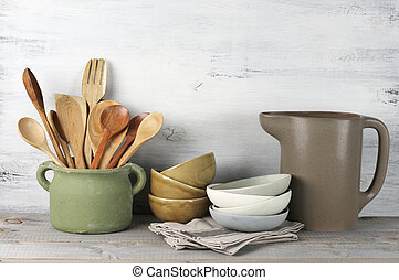 Simple rustic kitchenware against white wooden wall: rough ceramic pot with wooden cooking utensil set, stacks of ceramic bowls and jug.