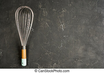 Kitchen Wire Whisk Eggs Beater on the dark concrete background with copy space. Flat lay background.
