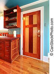 Kitchen with a beautiful wood door and hardwood floor.