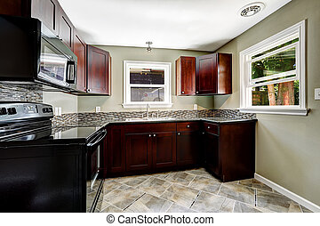 Kitchen with bright burgundy cabinets and black appliances.