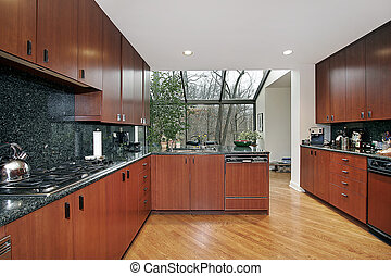 Wood paneled kitchen with glass enclosed eating area
