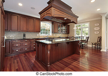 Kitchen with island stove - Kitchen in luxury home with...