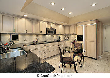 Kitchen with light oak cabinetry - Kitchen in townhouse with...