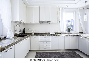 Kitchen with marble worktop - Interior of white kitchen with...