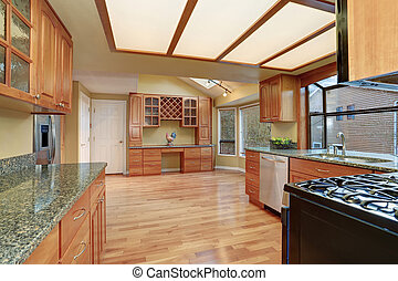 Kitchen with nice counters and stained cabinets.