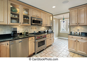 Kitchen with oak cabinetry - Kitchen in suburban home with...
