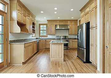 Kitchen in new construction home with oak wood cabinetry