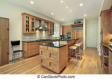 Kitchen with oak wood cabinetry - Kitchen in suburban home ...