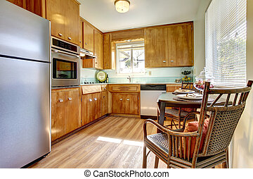 Kitchen with wood cabinets and chair.