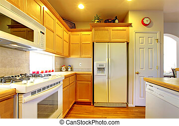 Kitchen with yellow wood cabinets and white appliances.