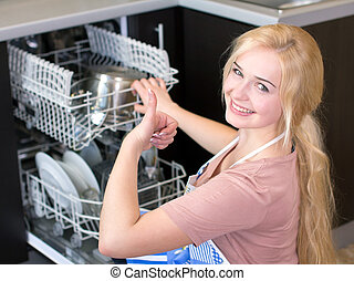 Kitchen Woman. Girl in the kitchen using dishwasher. view of...