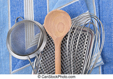 Kitchenware - Whisk, wooden spoon, grater and a colander on...