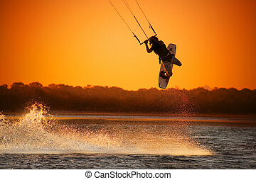 Kite boarder performing a jump at sunset