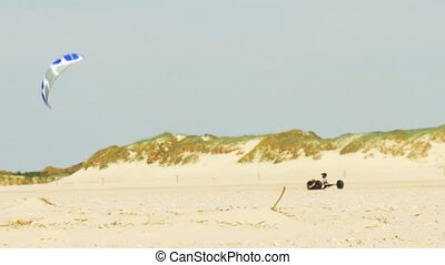 Kite buggying - A pilot in a buggy rolls through the deserted sandy beach