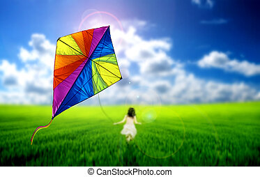 Kite flying - Child playing with a kite on a meadow