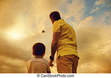 Father and son playing with a kite at sunset.