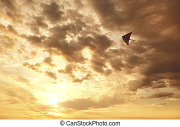 Kite flying in the sky with clouds at sunset