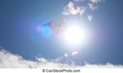 Kite flying on the blue sky against the sun. Kite flying in...