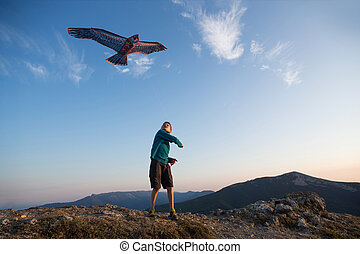Kite flying. The boy launches a kite. Beautiful sunset. Mountains, sea, landscape. Summer day, sunny.