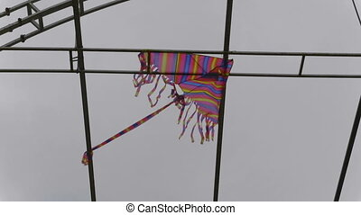 Kite is stuck in the metal structure against the sky....