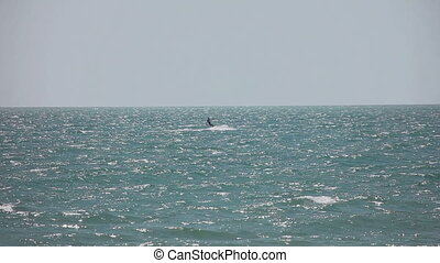Kite surfer in ocean - Kite surfer surfing on the waves with...