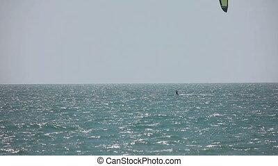 Kite surfer in ocean - Kitesurfer surfing on the waves with...