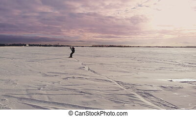 Kite surfing on a frozen lake in winter at sunset.