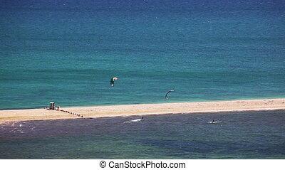 kite surfing on blue sea surface - kite surfing. surfers on...