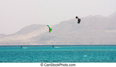 Kite surfing - Two kite surfers, blue sea and mount...