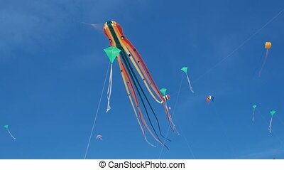 Kite with colorful stripes in shape of octopus in flight. Blue sky and sunny day.