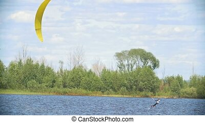 Kitesurfer moving on the river on the kiteboard with sail,...