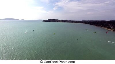 Kitesurfing on tropical island. Aerial view:kitesurfer sea rider rides at high speed. Travel concept. Thailand, Phuket. 4K video