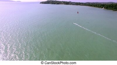 Kitesurfing on tropical island. Aerial view:kitesurfer sea rider rides at high speed. Travel concept. Thailand, Phuket. 4K video