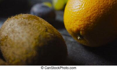 Kiwi and Orange Fruit on Dark Wooden Table
