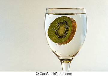 Kiwi covered with bubbles of gas in a glass on a light blurred background