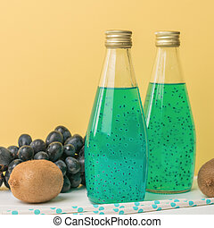 Kiwi fruit, blue grapes and two bottles of exotic cocktail on a yellow background.