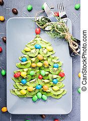 Kiwi fruit Christmas tree dessert on plate.