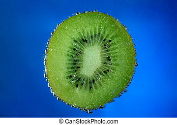 Kiwi fruit covered with bubbles on blue background