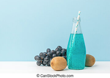 Kiwi fruit, grapes and a bottle of blue cocktail on a white table on a blue background.