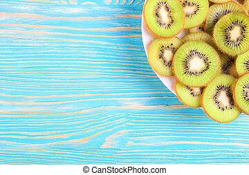 kiwi fruit on blue wooden background.