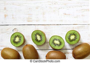 Kiwi fruit on white wooden background