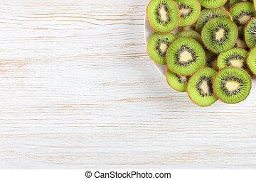 kiwi fruit on white wooden background.