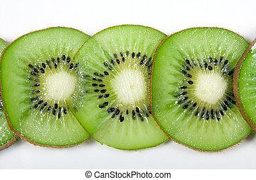 Slices of green kiwi fruit against white background