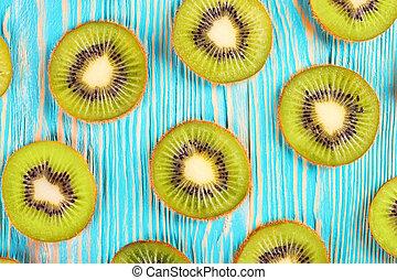 kiwi fruit slices on blue wooden background.