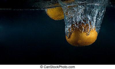 kiwi fruit splashing in the water