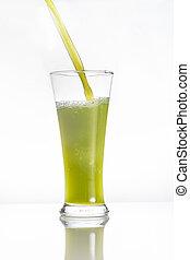 kiwi juice pouring into a glass on white