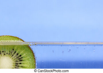 Closeup of a kiwi slice floating in sparkling water against an aqua blue background