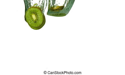 Kiwi slices plunging into water on white background in slow...