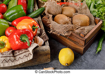 Kiwies and colorful vegetables in a wooden tray.
