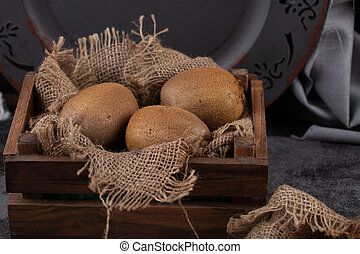 Kiwies in a rustic wooden tray.